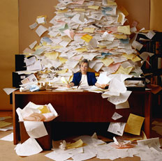 Lady at Messy Desk needing Bookkeeping Services and Accounting Services from Benchmark Bookkeeping